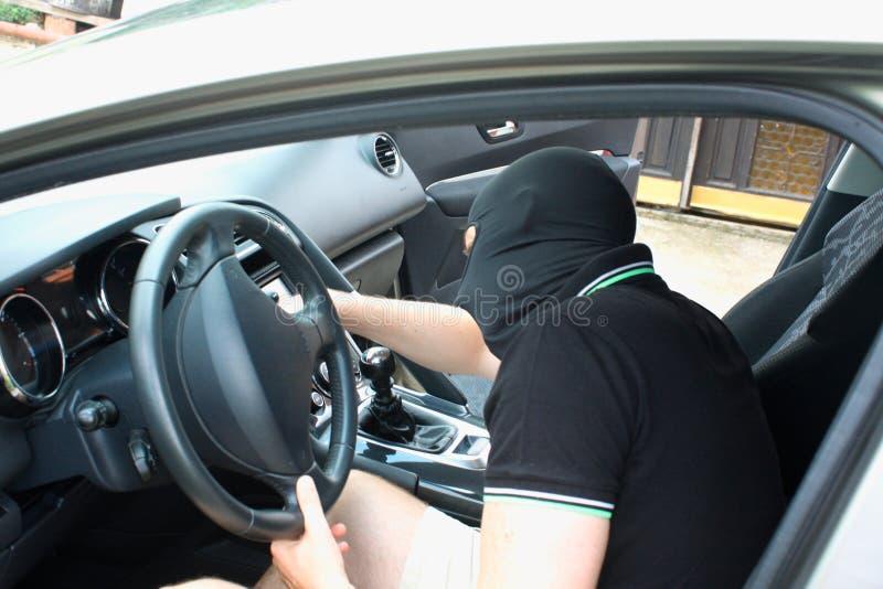 Il malfattore nella maschera che ruba automobile immagine stock