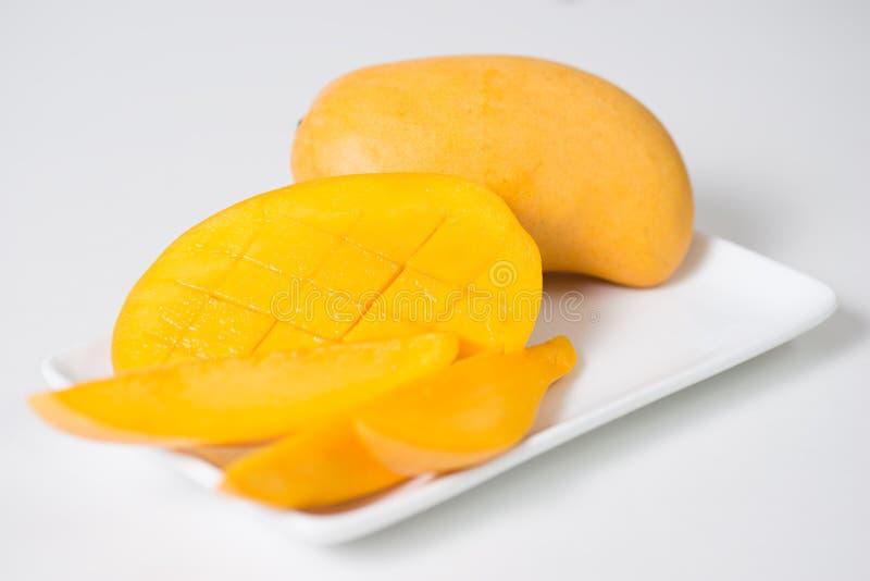 Il mango e le fette gialli di mango sono sul piatto bianco Fondo isolato immagine stock libera da diritti
