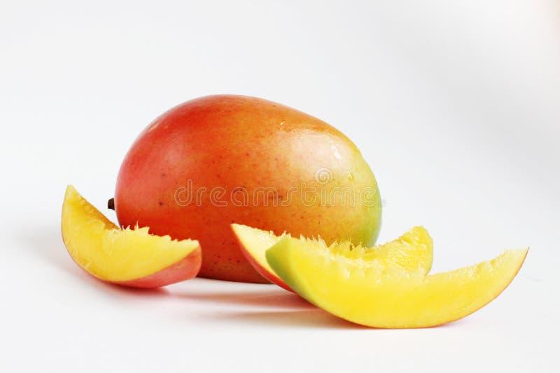Il mango succoso affetta il fondo bianco isolato immagini stock