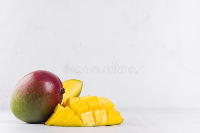Il mango succoso con giallo maturo ha affettato la metà sul fondo di legno bianco della luce morbida immagini stock libere da diritti