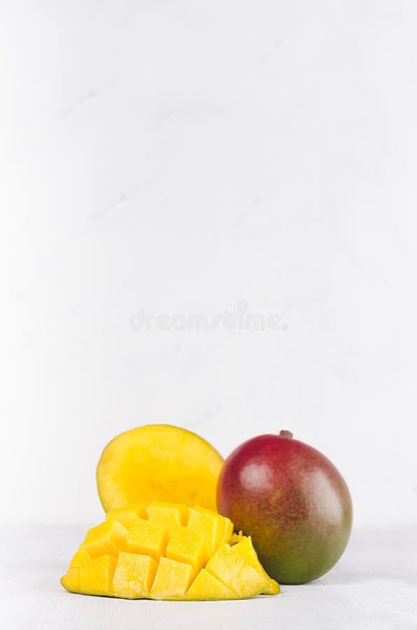 Il mango succoso con giallo maturo ha affettato la metà sul fondo di legno bianco della luce morbida, verticale fotografie stock libere da diritti
