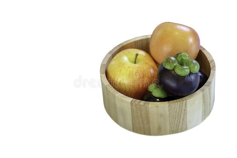 Il mangostano e la mela isolati hanno fatto da plastica in piastrina di legno su un fondo bianco con il percorso di ritaglio immagini stock libere da diritti