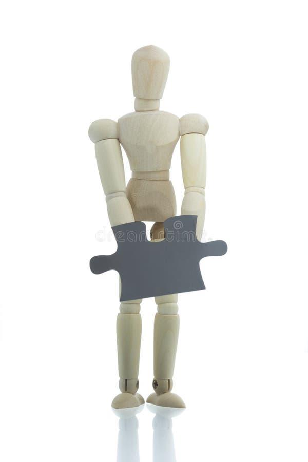 Il manichino tiene il pezzo di puzzle fotografia stock libera da diritti