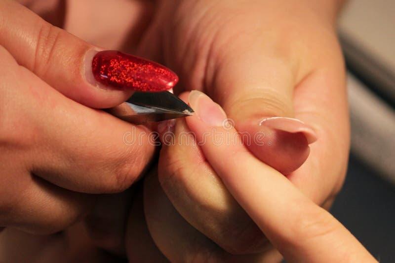 Il manicure ai corsi di formazione mostra a studenti come trattare i chiodi con l'aiuto delle cuticole delle pinze prima dell'app immagini stock
