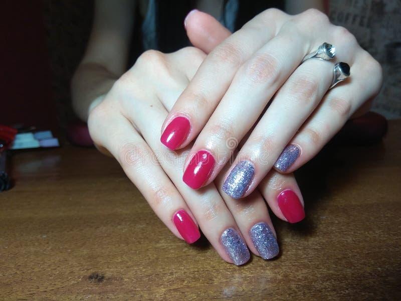 Il manicure eccellentemente ha reso al suo lavoro un bello manicure con un gel polacco sulle sue mani ed il cliente è felice immagini stock