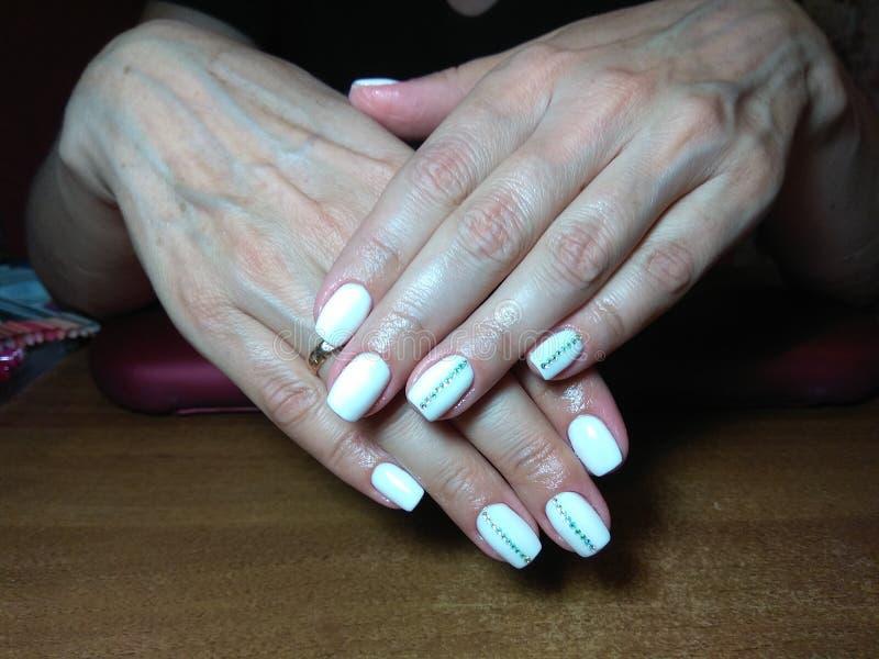 Il manicure eccellentemente ha reso al suo lavoro un bello manicure con un gel polacco sulle sue mani ed il cliente è felice immagine stock libera da diritti