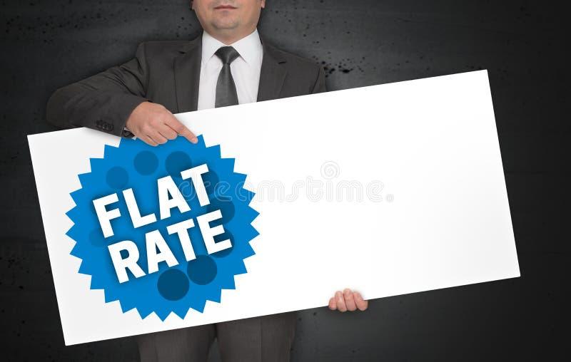 Il manifesto di aliquota forfettaria è tenuto dall'uomo d'affari fotografia stock libera da diritti