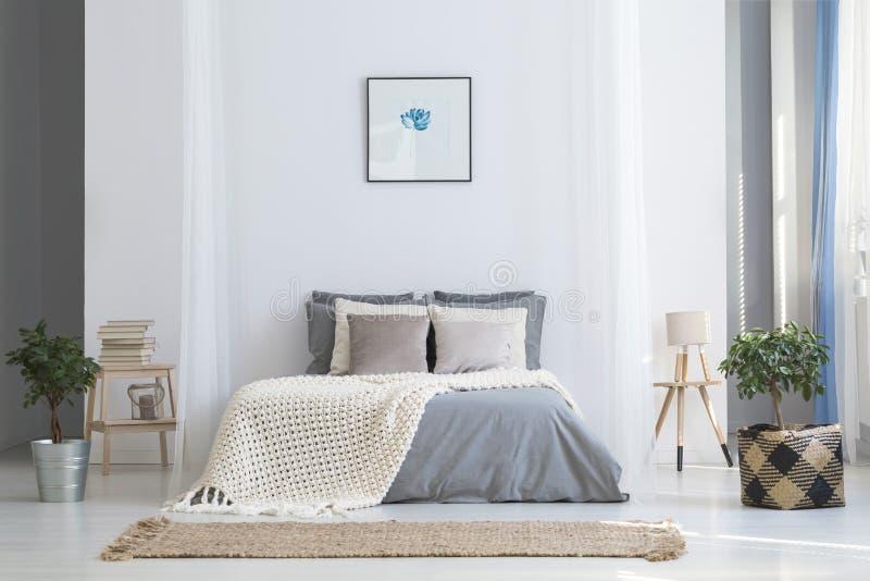 Il manifesto semplice sopra il letto con tricotta la coperta nel inte luminoso della camera da letto fotografie stock libere da diritti