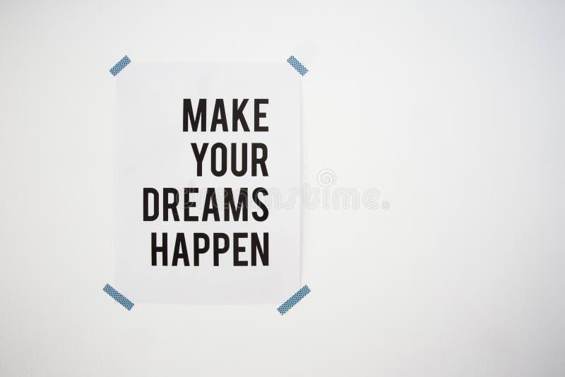 Il manifesto sulla parete bianca con la citazione fa i vostri sogni accadere struttura astratta del fondo fotografia stock