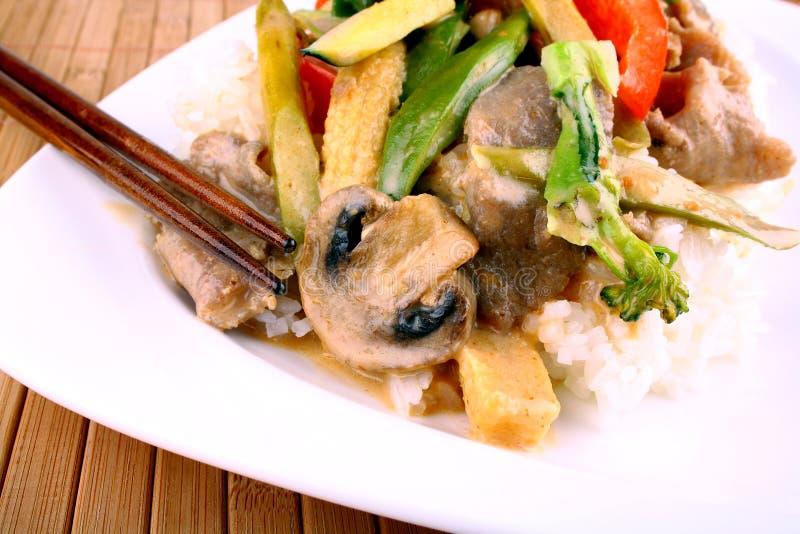 Il manzo con le verdure asiatiche, il riso, i funghi e l'arachide sauce immagine stock