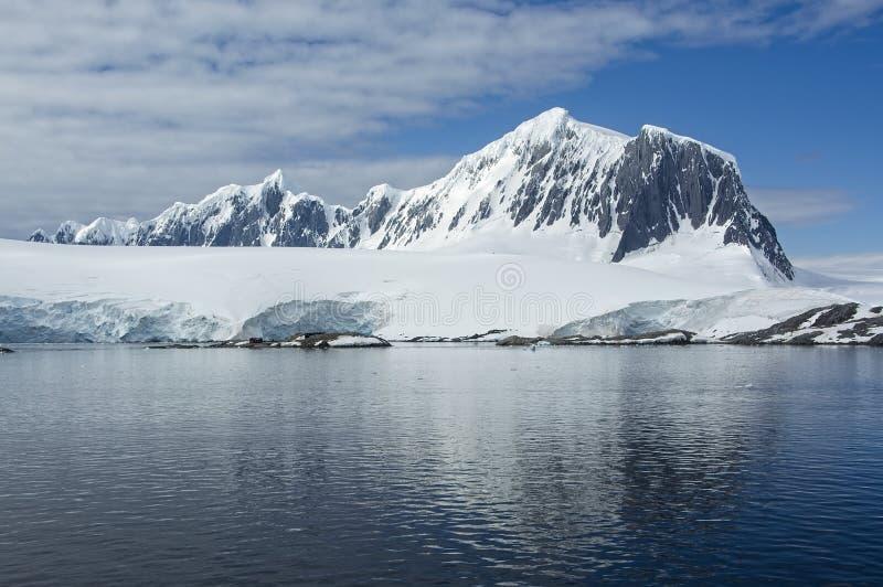 Il mare antartico riflette la montagna innevata fotografia stock