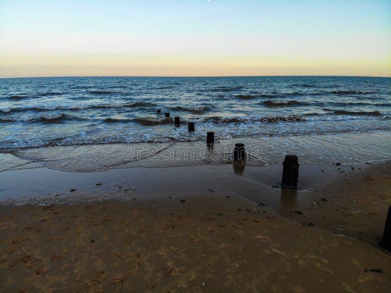 il mare dell'inguine ondeggia sabbia blu del tramonto dell'acqua della sabbia dell'oceano del mare la bella fotografia stock libera da diritti