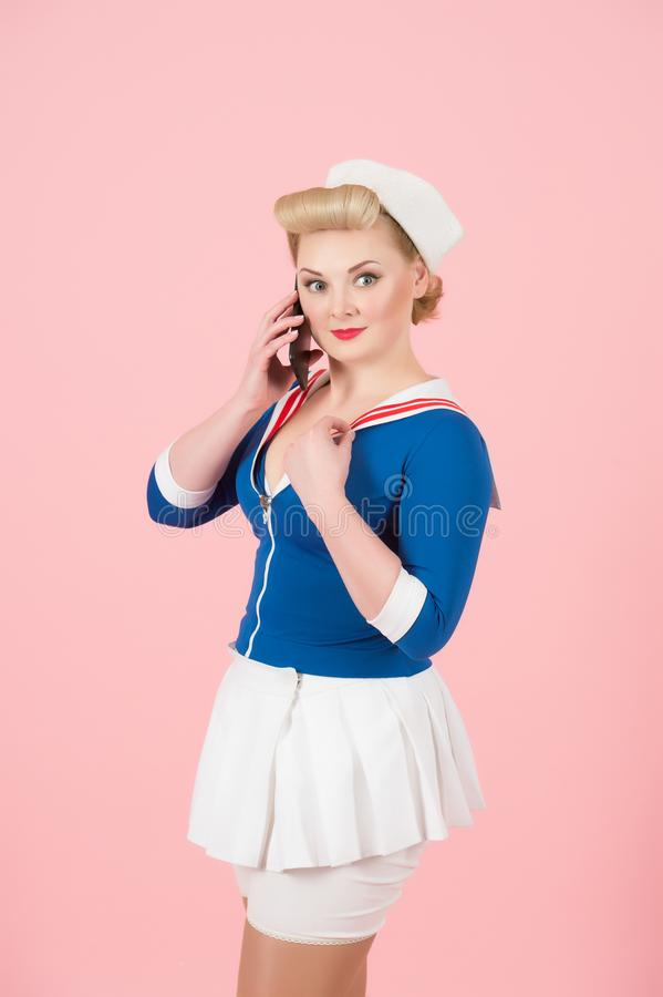 Il marinaio ha vestito la femmina con lo Smart Phone su fondo rosa La ragazza bionda con i riccioli e la pin-up preparano discute immagine stock libera da diritti