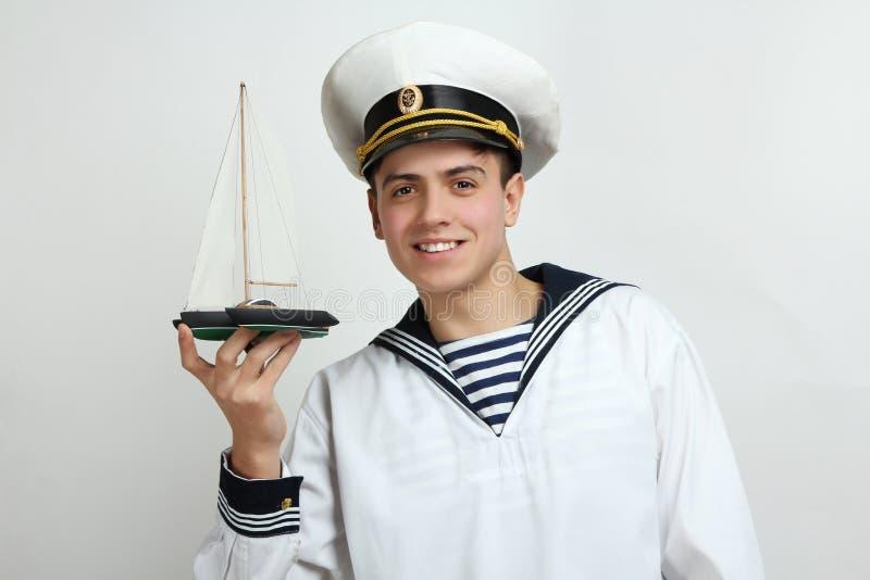 Il marinaio tiene una nave decorativa immagine stock