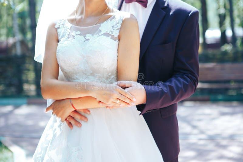 Il marito abbraccia la sposa dietro il suo sposo della vita abbraccia la sposa da dietro immagini stock