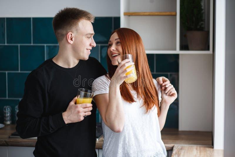 Il marito abbraccia la sua moglie E tengono in loro mani un vetro di succo d'arancia immagine stock libera da diritti