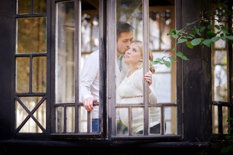 Il marito bacia la sua moglie incinta nella casa Vista attraverso la finestra immagine stock