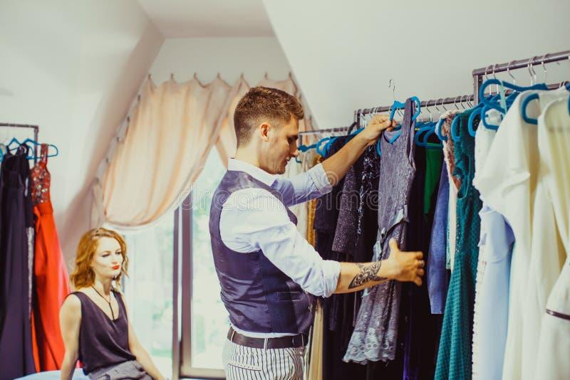 Il marito contribuisce a scegliere il vestito per la sua moglie immagine stock libera da diritti