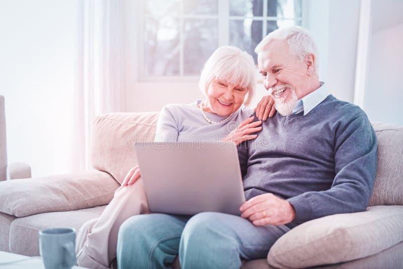 Il marito e la moglie in pensione che ridono guardando la commedia sul computer fotografia stock