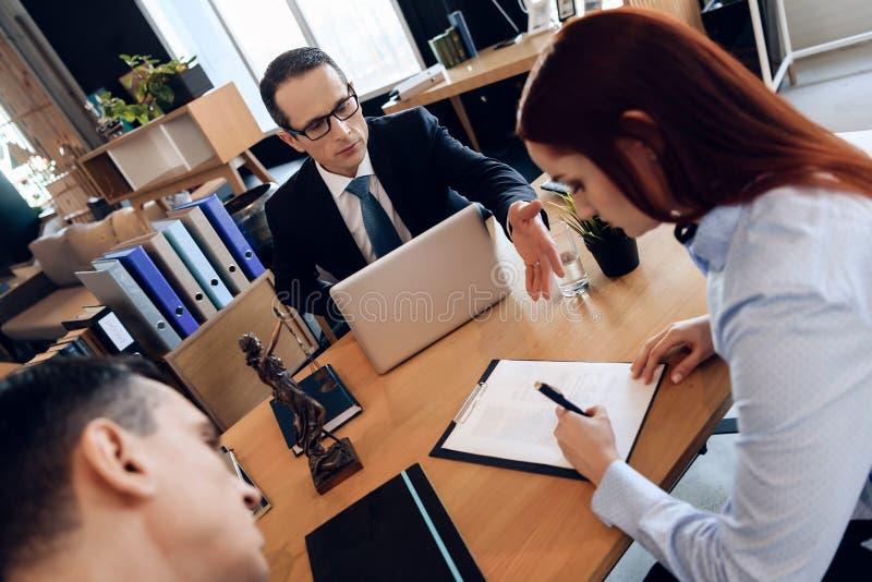 Il marito e la moglie stanno firmando lo stabilimento di divorzio Coppie che passano attraverso le carte di firma di divorzio fotografia stock libera da diritti