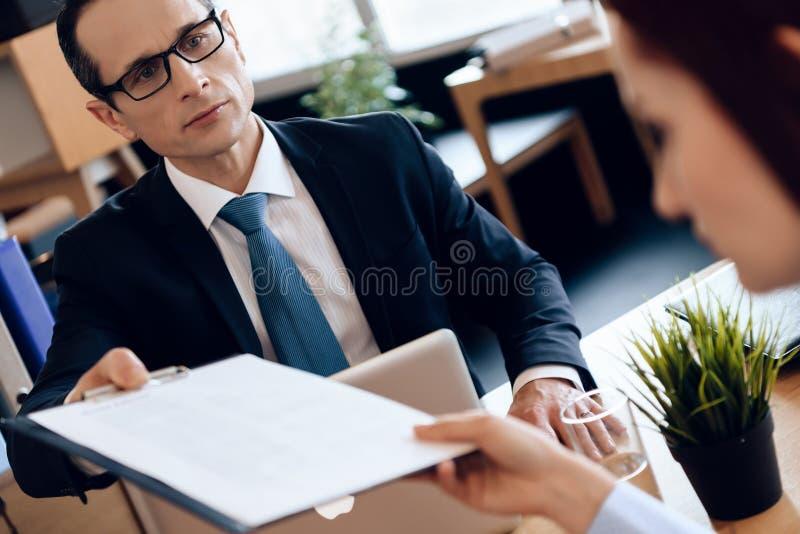 Il marito e la moglie stanno firmando lo stabilimento di divorzio Coppie che passano attraverso le carte di firma di divorzio fotografia stock