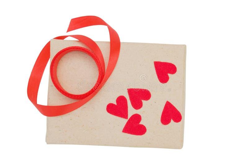 Il marrone d'annata ha avvolto il contenitore di regalo con il nastro rosso ed il cuore da carta isolata su fondo bianco fotografia stock libera da diritti
