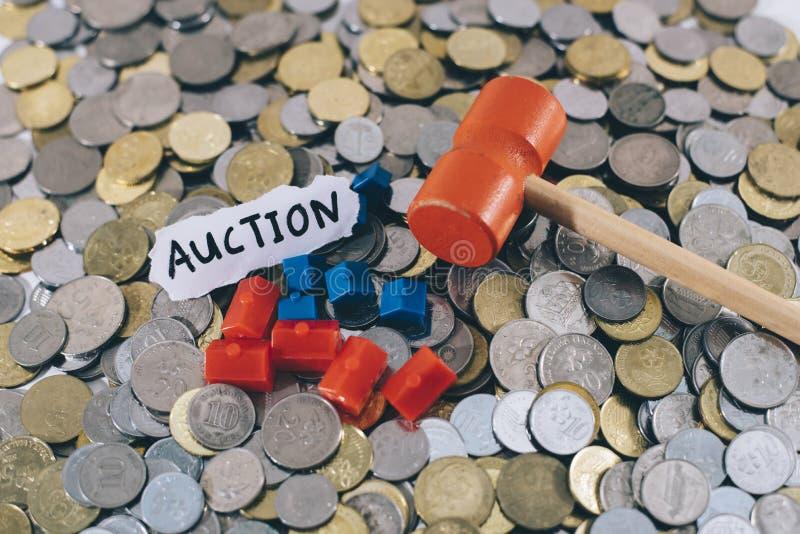 Il martello di legno e la casa miniatura su un gruppo di monete con ` scritto nota mettono all'asta il ` fotografia stock