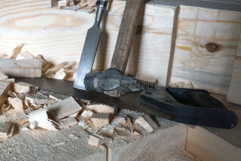 Il martello, la sega e lo scalpello sono sui bordi immagini stock