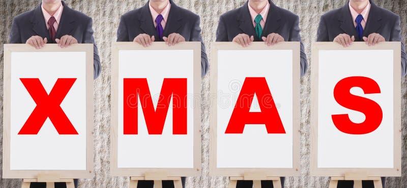 Il MAS di manifestazione X dell'uomo d'affari manda un sms a per chritmasday benvenuto immagine stock