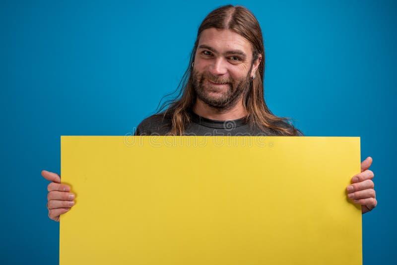 Il maschio adulto che fa i fronti divertenti alla macchina fotografica mentre tiene un giallo annuncia l'insegna fotografia stock libera da diritti