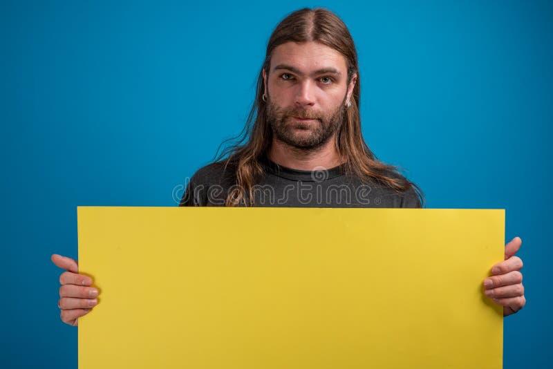 Il maschio adulto che sembra serio alla macchina fotografica mentre tiene un giallo annuncia l'insegna immagine stock libera da diritti