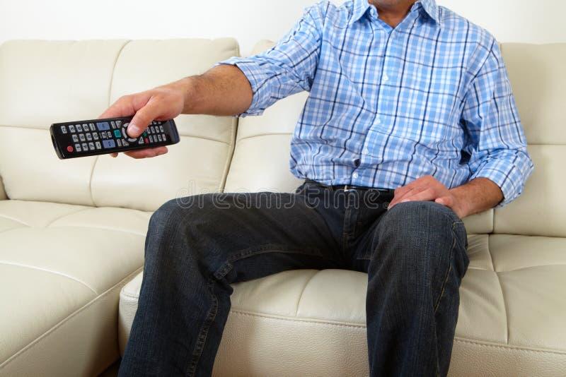 Il maschio adulto che si siede sul sofà e vede la TV fotografie stock libere da diritti