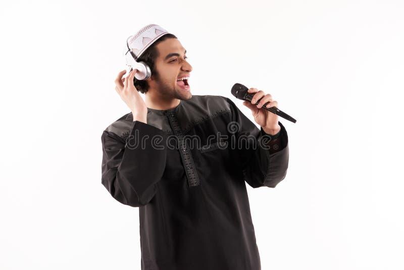 Il maschio arabo in vestito etnico sta cantando nel karaoke immagini stock libere da diritti
