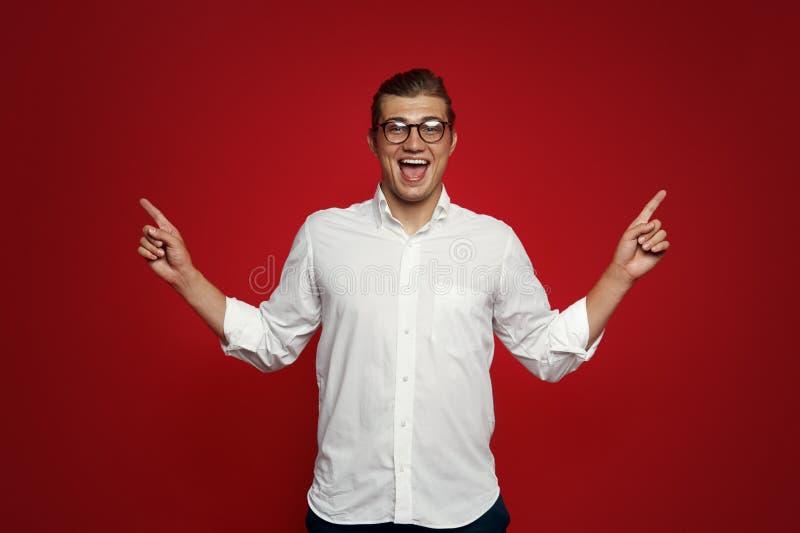 Il maschio attraente allegro indica con entrambe le dita anteriori su, ha sorriso amichevole, mostra lo spazio contro fondo rosso immagini stock