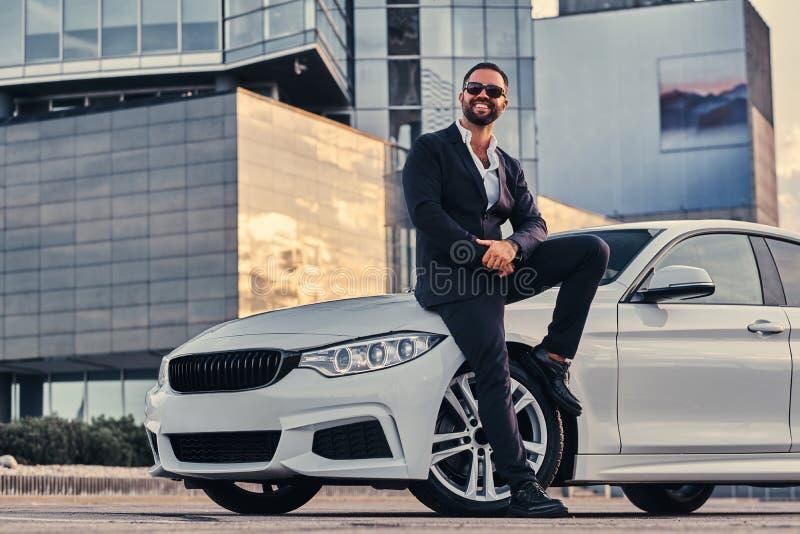 Il maschio barbuto bello felice in occhiali da sole si è vestito in un vestito nero che si siede sull'automobile di lusso contro  fotografia stock