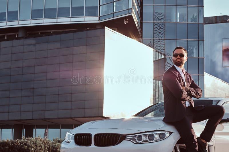 Il maschio barbuto bello in occhiali da sole si è vestito in un vestito nero che si siede sull'automobile di lusso contro un grat fotografia stock libera da diritti