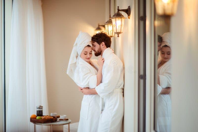Il maschio barbuto e la sua moglie porta gli accappatoi bianchi e l'asciugamano sulla testa, si abbraccia, tatto rilassato dopo l fotografia stock