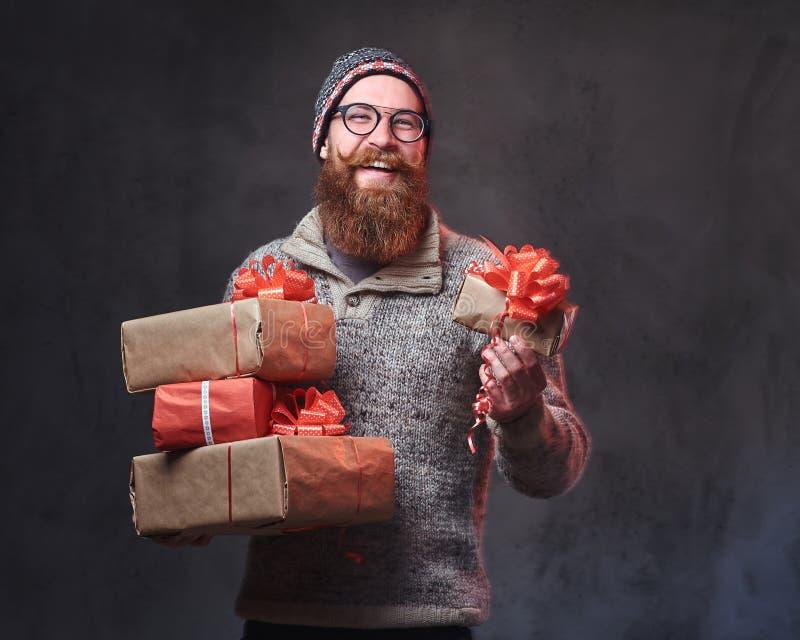 Il maschio barbuto tiene i regali di Natale immagini stock libere da diritti