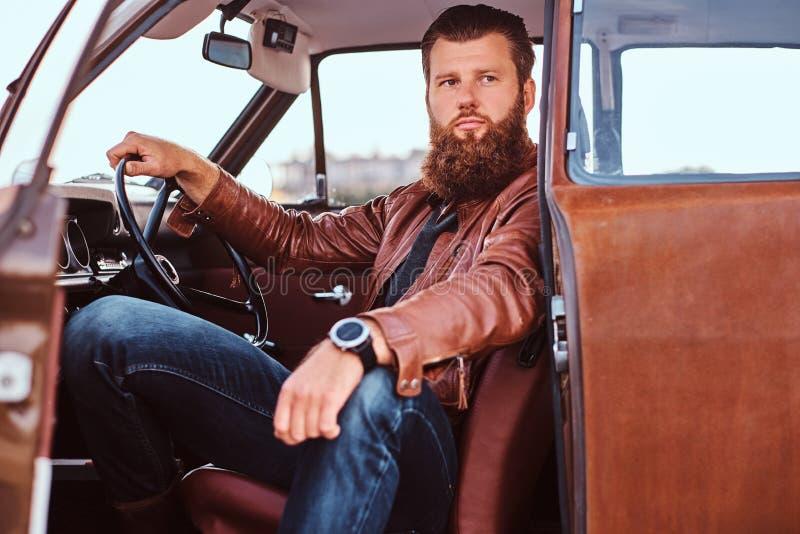 Il maschio barbuto vestito in bomber marrone si siede dietro la ruota di retro automobile sintonizzata con la porta aperta immagine stock libera da diritti