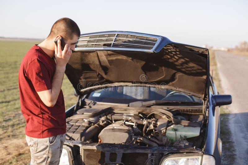 Il maschio bello sta vicino solo brocken l'automobile, richieste per assistenza della strada di sostegno, aiuto di bisogno, può ` immagini stock libere da diritti