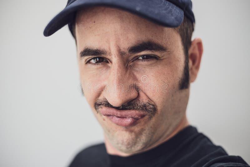 Il maschio bianco con i baffi e un cappello contro un fondo senza cuciture esamina la macchina fotografica con uno sguardo impert immagine stock libera da diritti