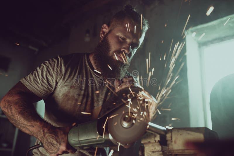 Il maschio brutale bello con una barba che ripara un motociclo nel suo funzionamento del garage con una circolare ha visto Nel ga immagine stock libera da diritti