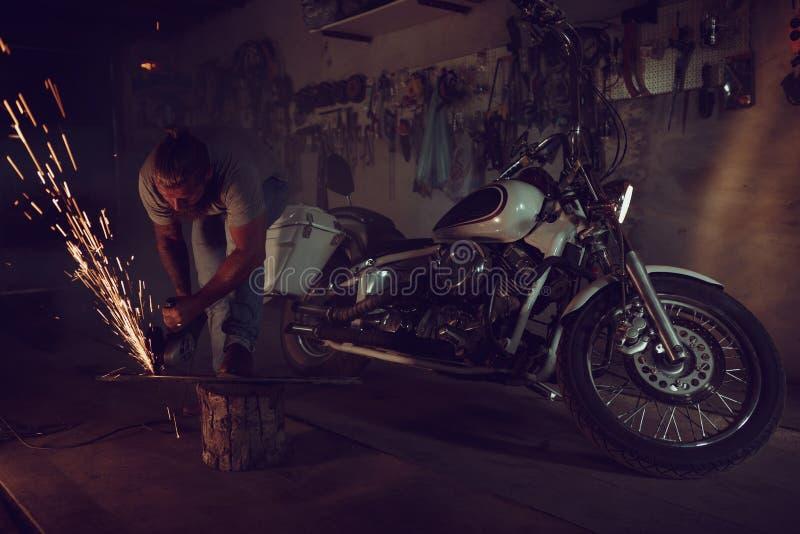 Il maschio brutale bello con una barba che ripara un motociclo nel suo funzionamento del garage con una circolare ha visto Nel ga fotografia stock libera da diritti