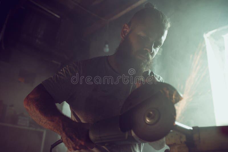 Il maschio brutale bello con una barba che ripara un motociclo nel suo funzionamento del garage con una circolare ha visto Nel ga fotografia stock