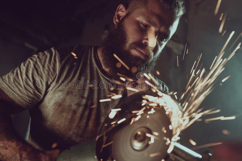Il maschio brutale bello con una barba che ripara un motociclo nel suo funzionamento del garage con una circolare ha visto Nel ga fotografie stock libere da diritti