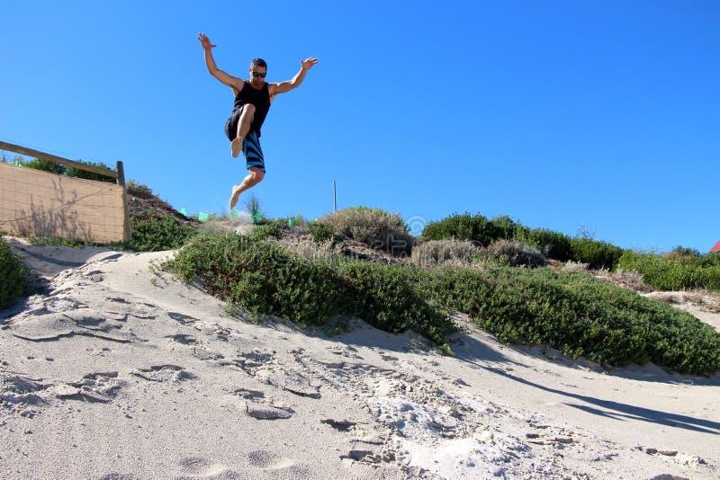 Il maschio che salta giù le dune di sabbia a Cottesloe tira fotografia stock
