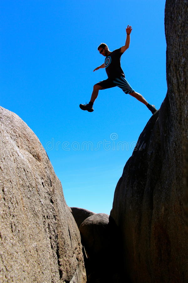 Il maschio di scheletro della baia della Tasmania della costa Est salta da roccia a roccia fotografia stock libera da diritti