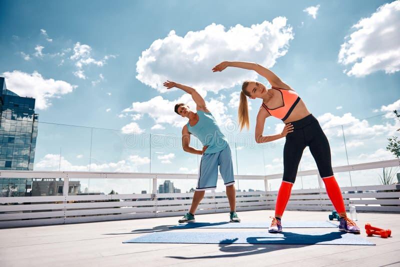 Il maschio e la femmina sportivi stanno facendo la forma fisica sul tetto fotografia stock