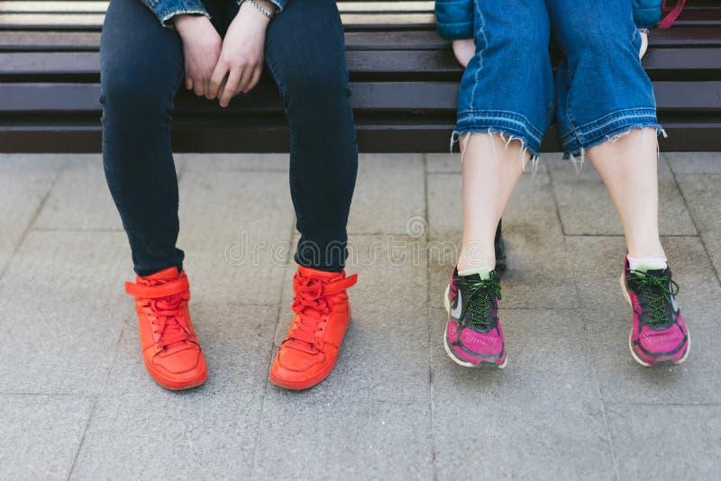 Il maschio e le gambe femminili in scarpe da tennis luminose stanno sedendo su un banco fotografia stock