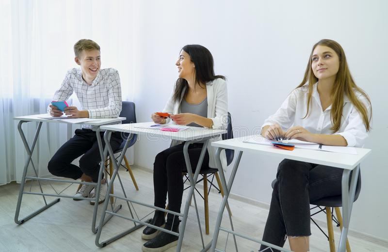Il maschio e le studentesse sorridenti positivi praticano il lavoro di squadra ed eseguono le abilità di comunicazione immagini stock libere da diritti